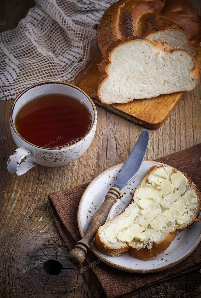Homemade bread with butter on wooden background