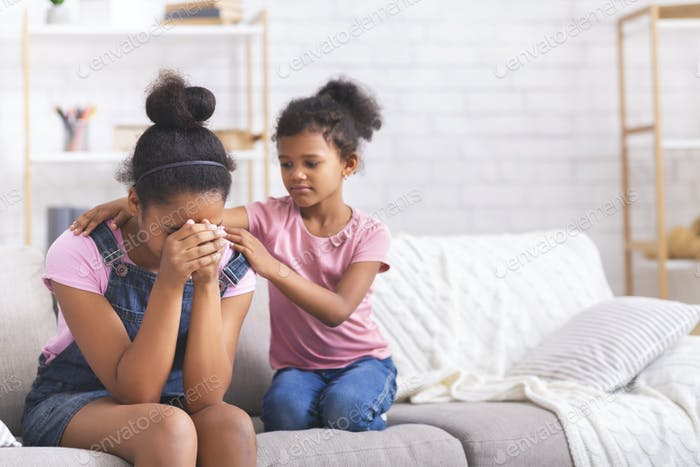Little african girl comforting her crying teen sister with relationship problems