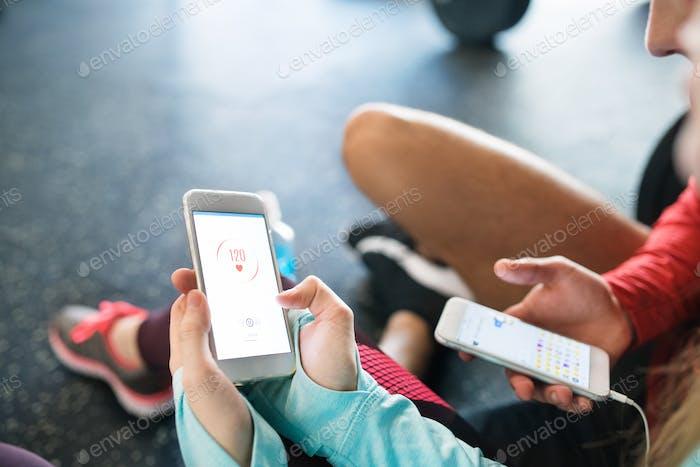 Unerkennbare Passform Paar im Fitnessstudio mit Smartphones.
