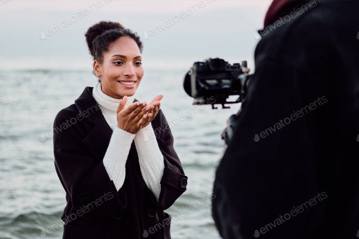 Cute African American girl happily sending air kiss on camera during photo session by the sea