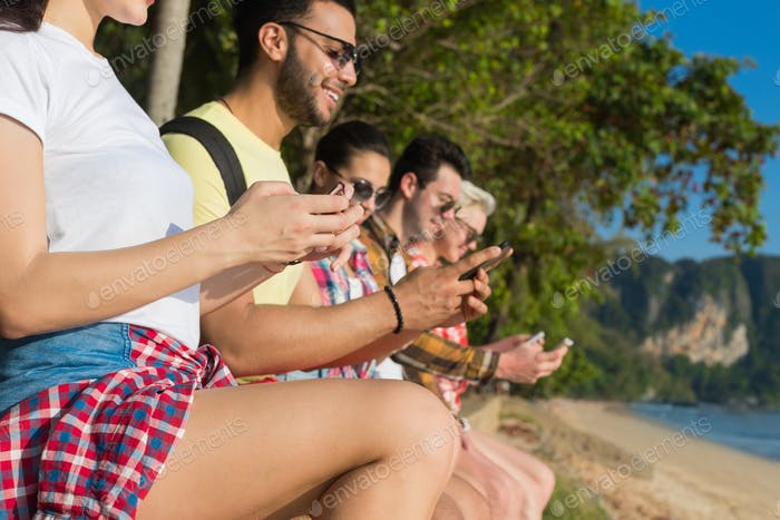 Young People Group Using Cell Smart Phones Tropical Park Palm Trees Friends Chatting Online Holiday