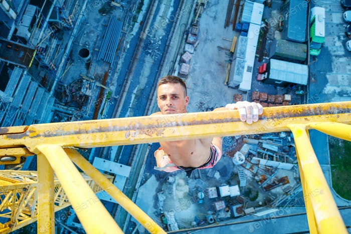 Rock climber hanging on jib of construction crane with one hand