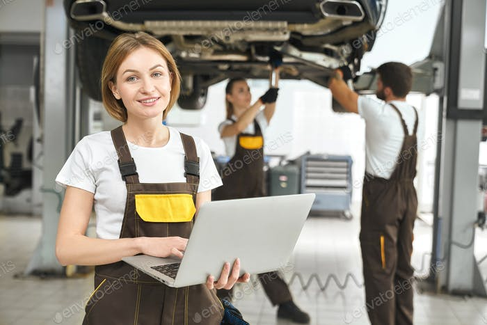 Pretty worker holding laptop, posing in autoservice