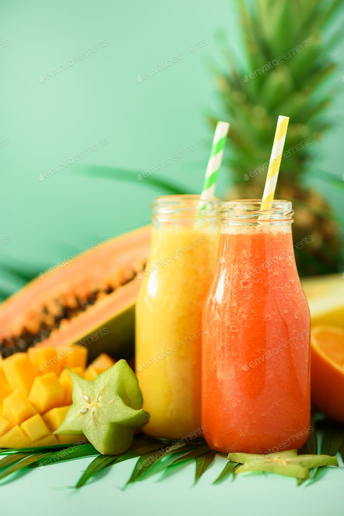 Saftiger Papaya und Ananas, Mango, Orangenfrucht-Smoothie in zwei Gläsern auf türkisfarbenem Hintergrund. Entgiftung
