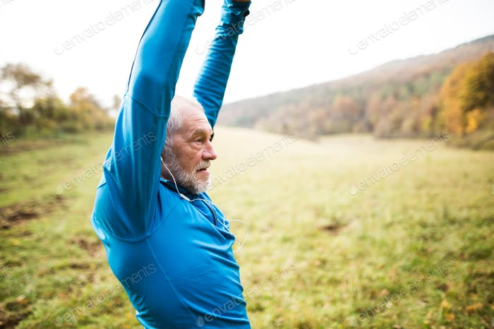 Senior runner with earphones doing stretching. Autumn nature.