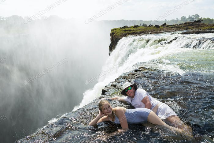 Man and a girl in the water of the Devil's Pool on the edge of Victoria Falls.