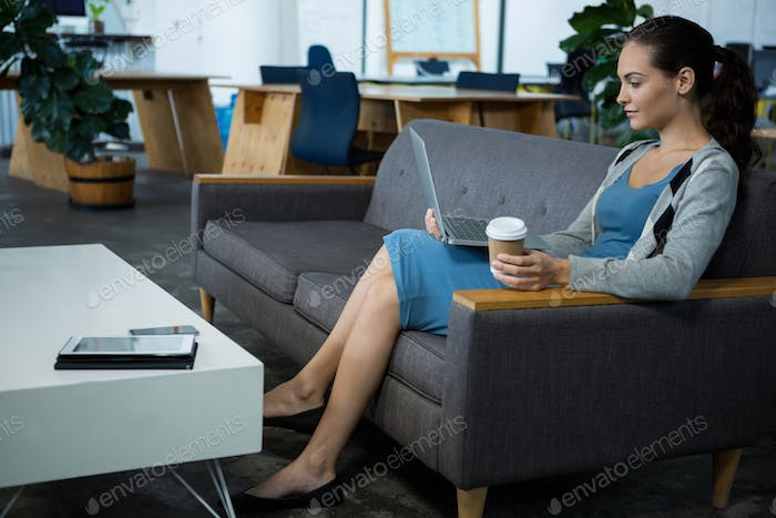 Female business executive using laptop