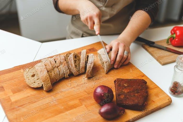 Weibliche Hände schneiden ein Stück Weizenbrot. Overhead-Ansicht