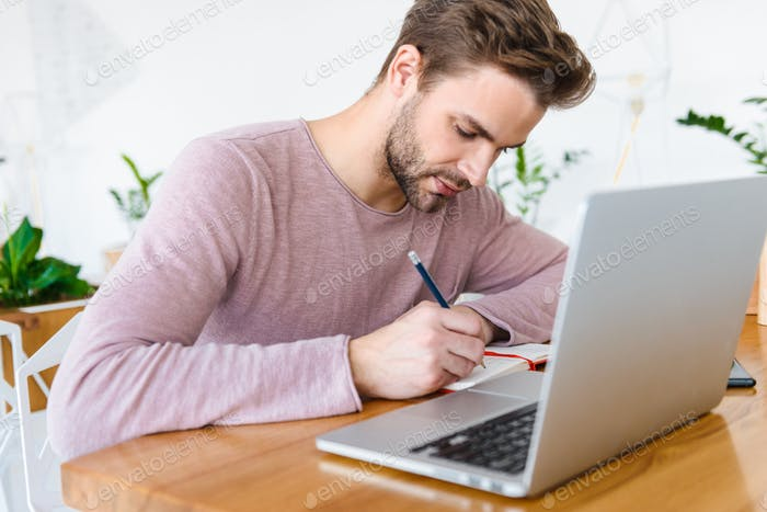 Image of young man working on laptop and using planner book in cafe