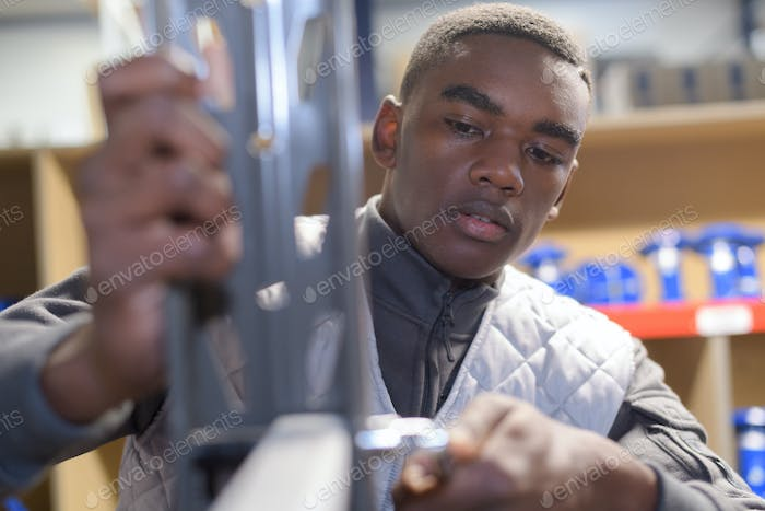 Young worker assembling metal components