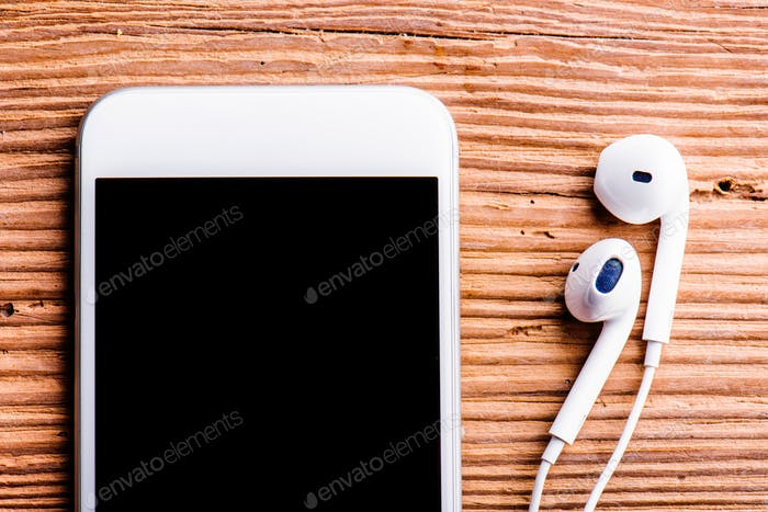 Smartphone and earphones laid on an old office desk