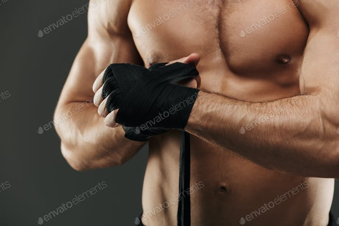 Close up of a muscular man tying boxing bandages