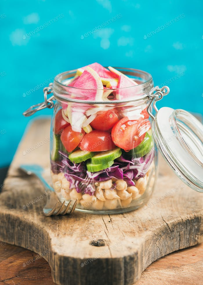Vegetable and chickpea sprout vegan salad in jar, blue background