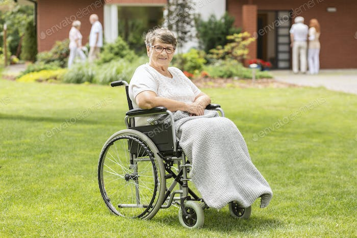 Happy disabled elderly woman in a wheelchair on green grass duri