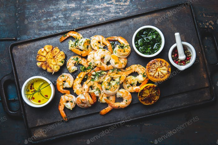 Roasted shrimps on frying board. top view