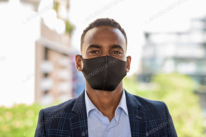 Face of young African businessman wearing mask for protection from corona virus outbreak against