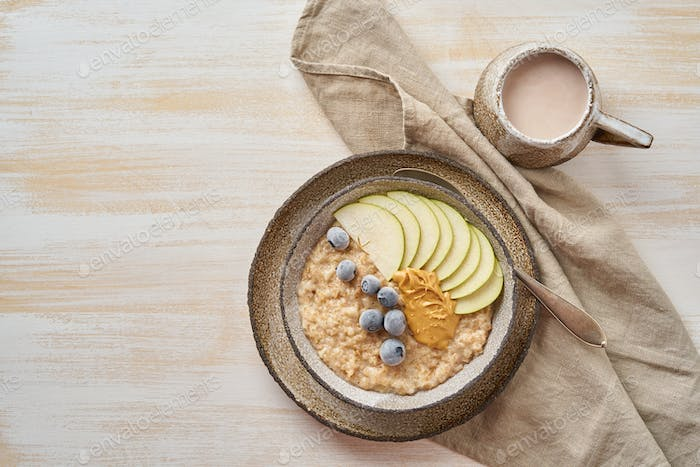 Oatmeal, healthy porridge in large bowl with fruits and berry for breakfast, cup of cocoa.