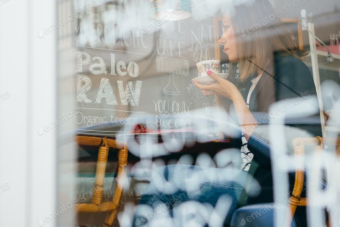 Pensive woman drinking tea in cafe