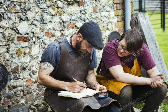 Two men wearing aprons writing into a notebook sat in a garden.