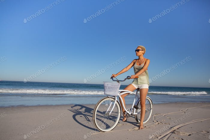 Beautiful African american woman in sunglasses sitting on bicycle at beach