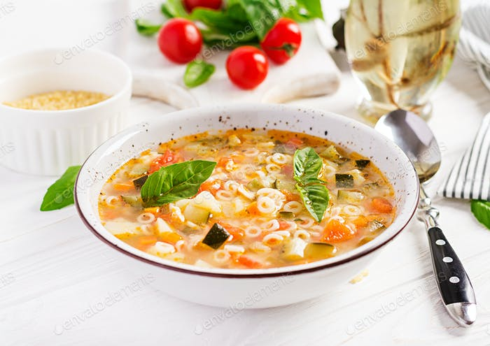 Minestrone, italian vegetable soup with pasta on white table. Vegan soup.
