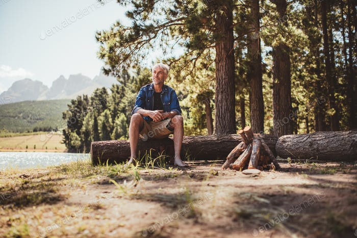 Mature man sitting on a log staring out to the lake