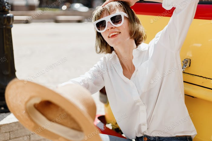 Stylish young woman in white sunglasses dressed in white shirt and jeans holding a straw hat in her