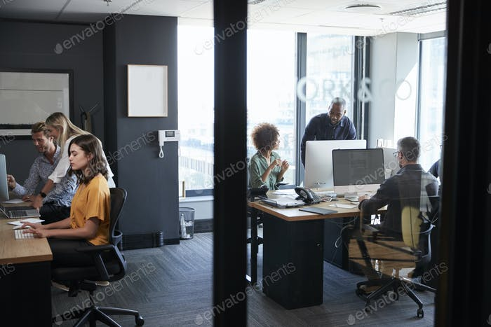 Young creative team working together at computers in a casual office, seen through glass wall