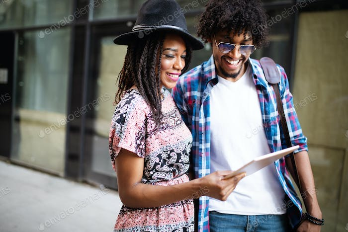 Young attractive african couple talking and looking at digital tablet