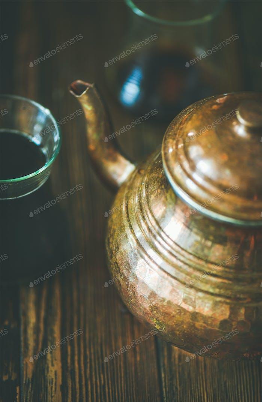 Orientalische Teekanne und schwarzer Tee in Tulpengläsern