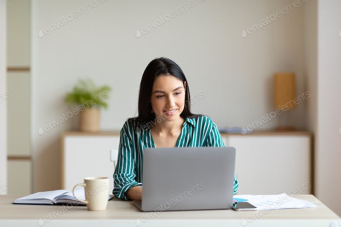 Businesswoman Working On Laptop Sitting At Workplace In Office
