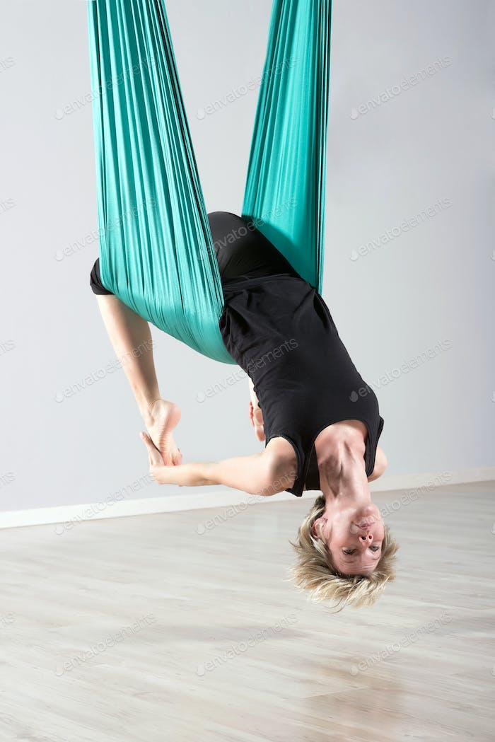 Upside down woman doing aerial yoga back bends