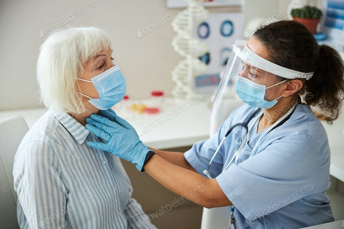 Un médico bien protegido está haciendo una palpación del cuello
