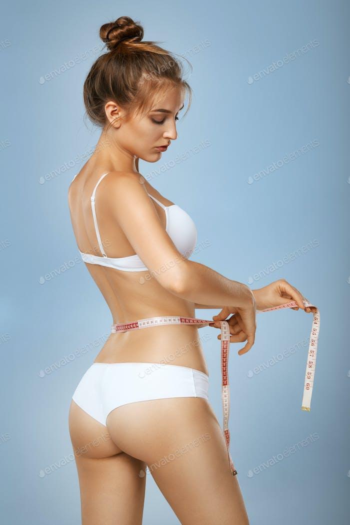 Slim tanned woman with measure tape around waist