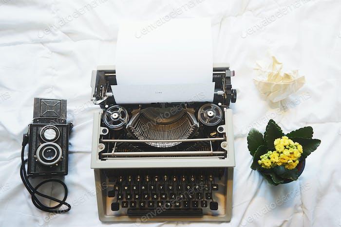 Vintage Schreibmaschine und Kamera auf dem Bett