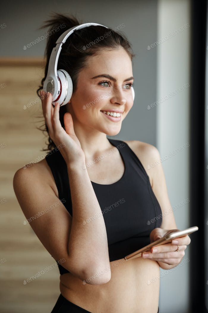 Photo of smiling seductive woman using headphones and smartphone