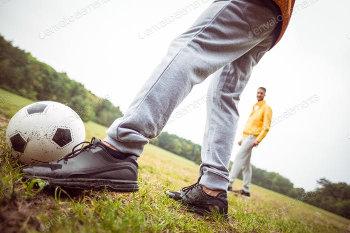 Friends playing football in the park in the countryside