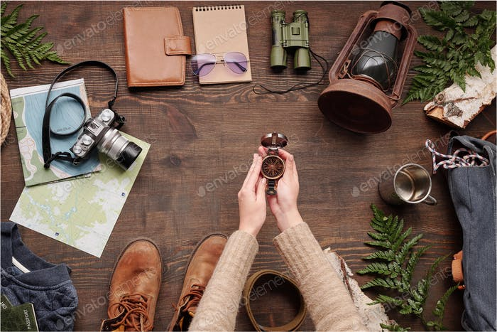 Hiker holding compass above table