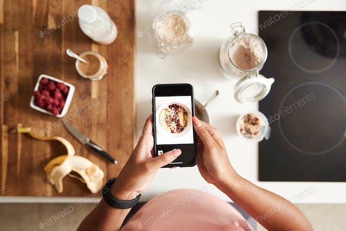 Overhead Shot von Frau, die Bild von gesundem Frühstück auf Handy zu Hause nach dem Training