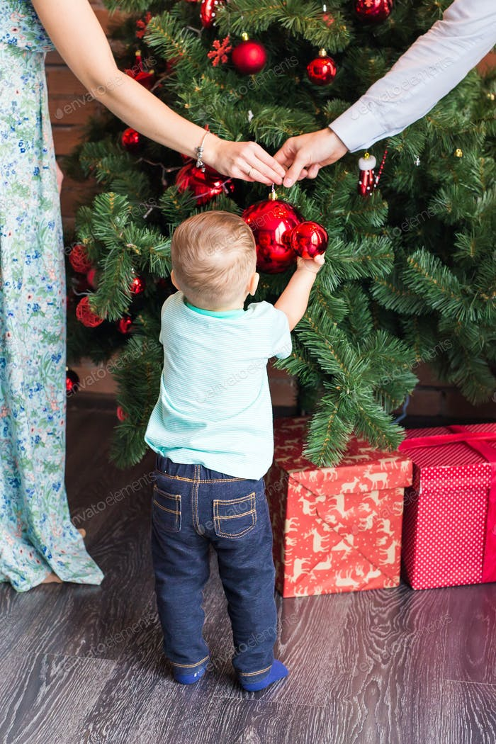 Little baby boy decorating a Christmas tree toys. Holidays, gift, and new year concept