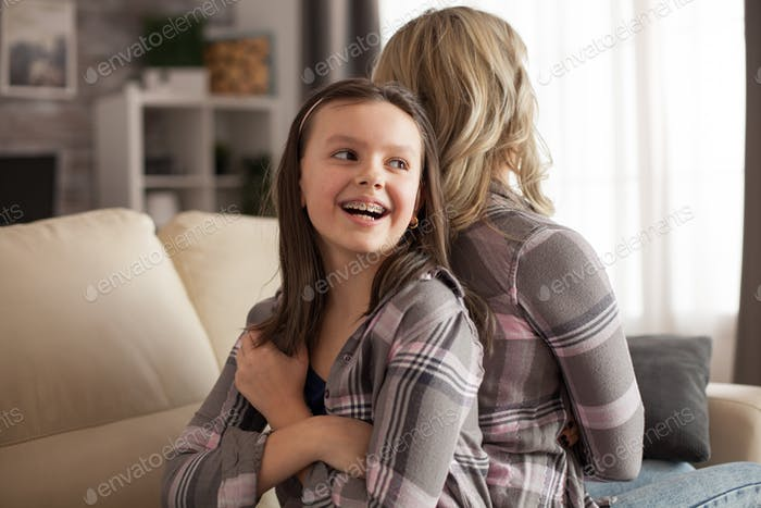 Little girl with a big smile and braces sitting back to back