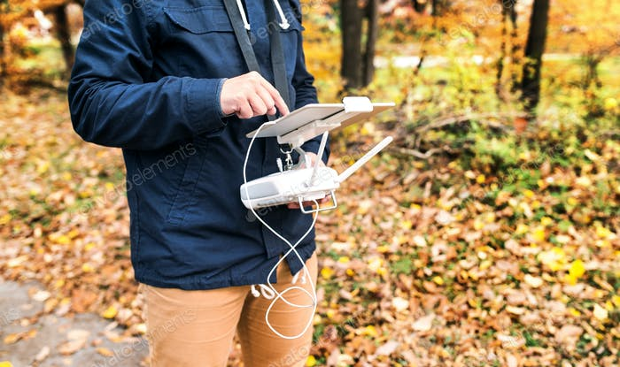 Man with tablet and drone controller in autumn park.