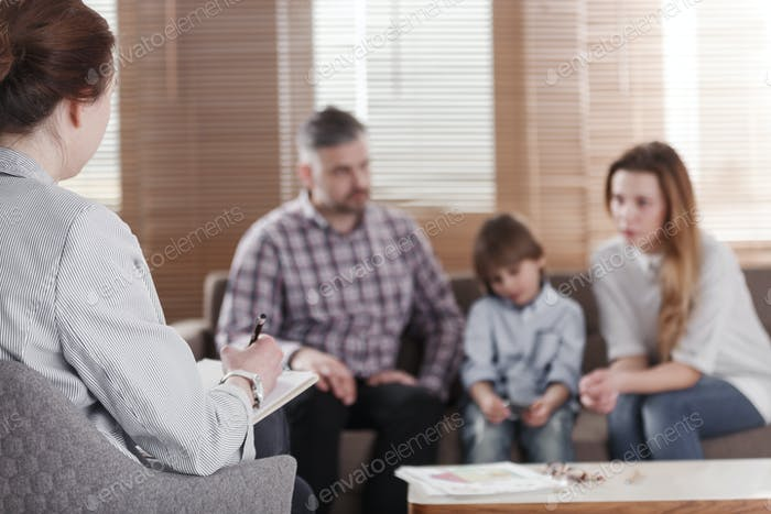 Rear view of female psychologist helping young family with a kid