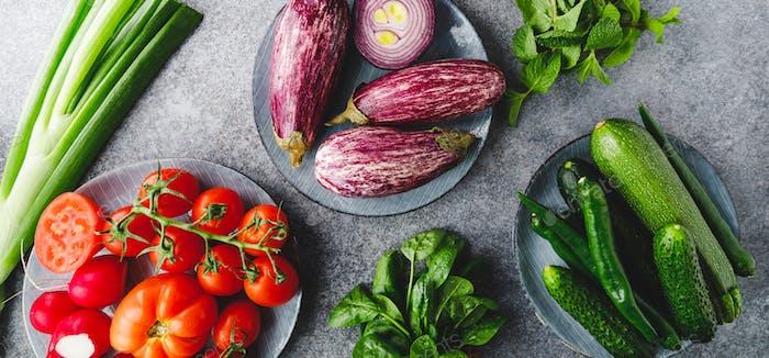 Grün, rot und lila verschiedene frisches Gemüse auf einem Tisch. Gesunde Ernährung Konzept