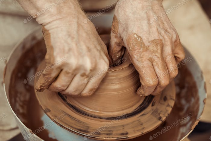 Close up of male craftsman working on potters wheel