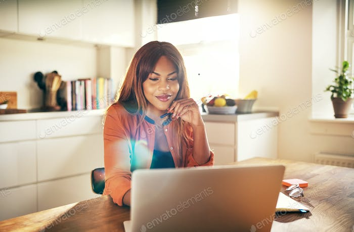 Successful female entrepreneur working on a laptop in her kitchen