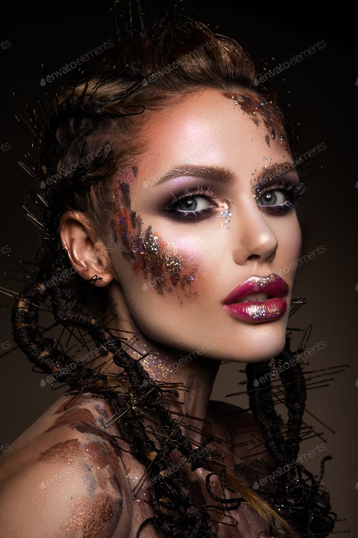 Fashion model with bright makeup and colorful glitter