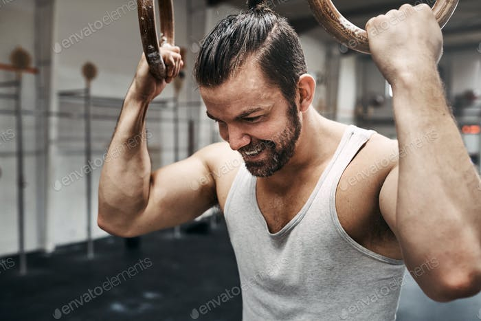 Smiling young man exercising with rings at the gym