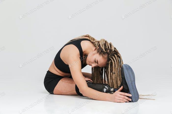 Gesunde junge behinderte Sportlerin machen Dehnungsübungen.