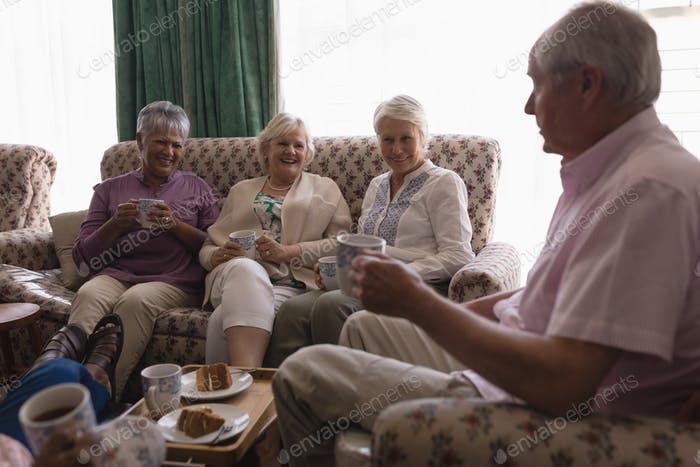 Side view of senior people having coffee and cake in living room at home